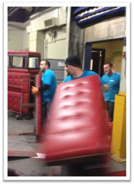 It took less than four hours to fill two shipping containers with Sheraton Boston surplus. Here NEOC movers are packing tables and seating.